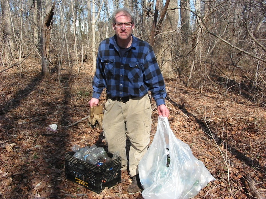 Sean Solomon proudly displays his recently gathered trash from the forest floor.  Morris Park, Philadelphia